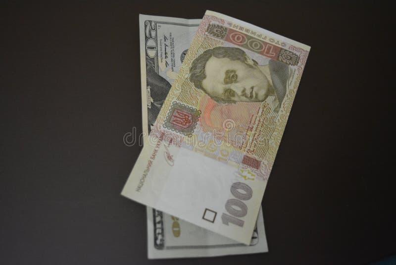 Cientos hryvnia y veinte dólares, dineros y mercados de las actividades bancarias, recursos para hacer negocio foto de archivo