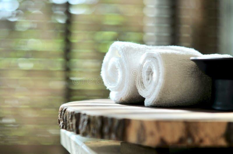 Ciepła atmosfera w zdroju kurorcie, zakończenie w górę zdrój podstaw i ręczniki na drewnianej tacy w łazience, istotny olej obrazy stock