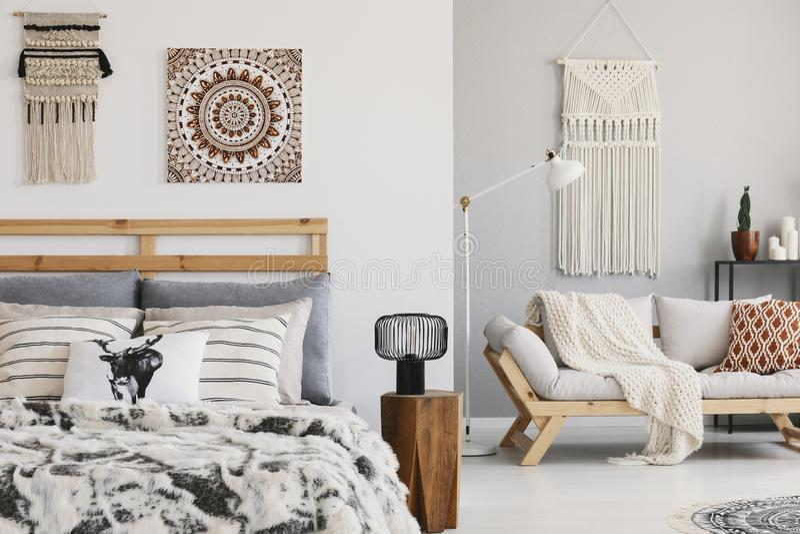 Ciepła ethno sypialnia z wzorzystymi poduszkami na, makrama na ścianie i zdjęcie stock
