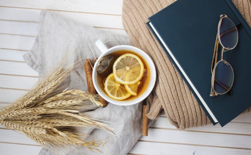 Ciepła herbaciana przerwa z cytryny, cynamonowych i wygodnych szczegółami, fotografia stock