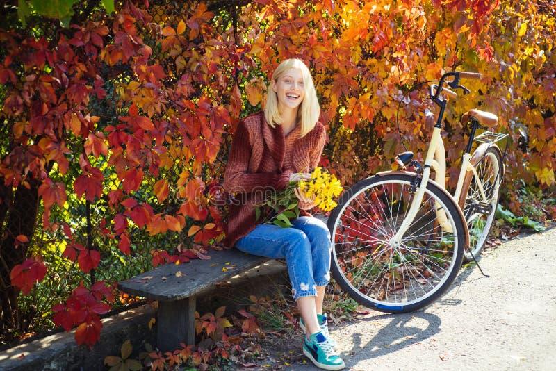 Ciep?a jesie? Dziewczyna z bicyklem i kwiatami Kobiety jesieni rowerowy ogr?d Aktywny czas wolny i styl ?ycia Jesień prosta fotografia stock