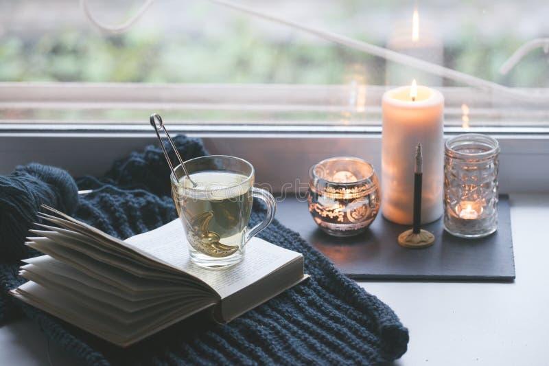 Ciep?y i comfy jesieni poj?cie Rezerwuje, fili?anka herbata i candlestick na nadokiennym parapecie w domu Czytelniczy i relaksują obraz royalty free