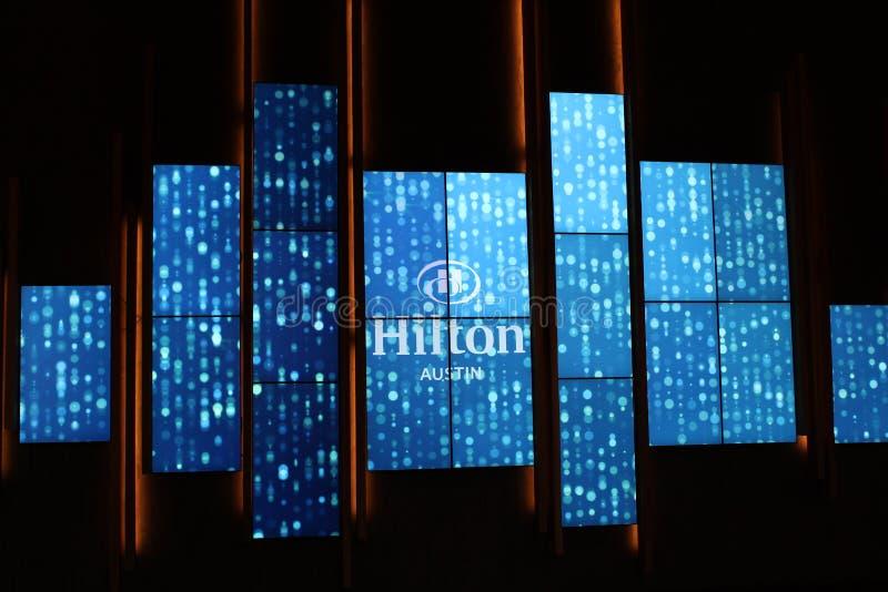 Ciepli i powitalni jaskrawi chodzenie znaka powitalni ludzie wśrodku błękitnego i białego Hilton, Austin, Teksas, 2018 zdjęcia stock