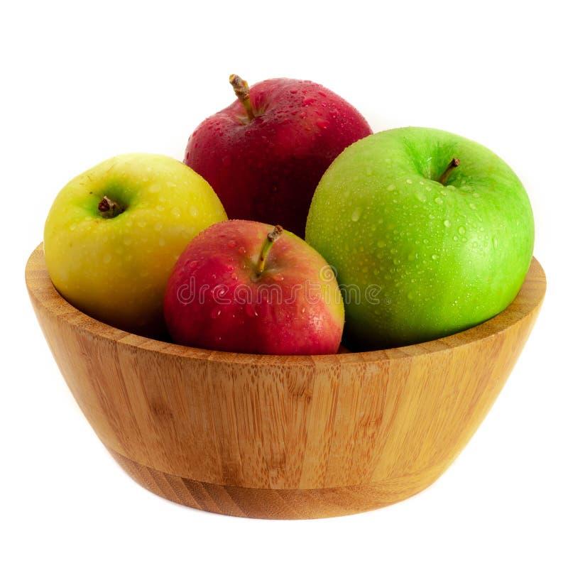 Ciepli koloru czerwieni, zieleni i koloru żółtego jabłka w drewnianym pucharze odizolowywającym na białym tle, fotografia royalty free