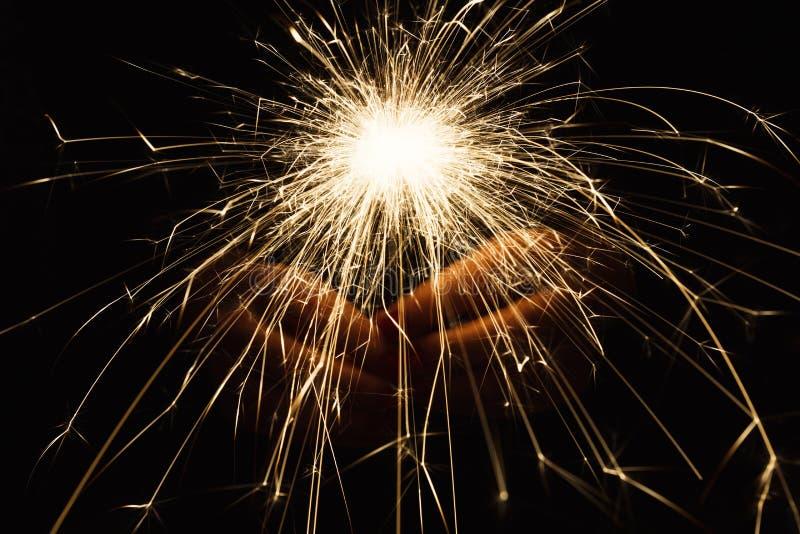 Cierge magique de partie de nouvelle année dans des mains femelles sur le fond noir images libres de droits