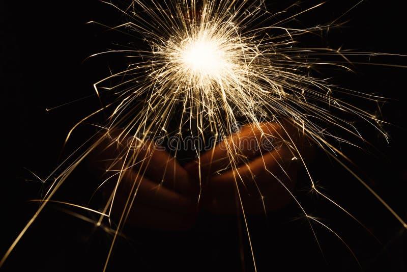 Cierge magique de partie de nouvelle année dans des mains femelles sur le fond noir images stock