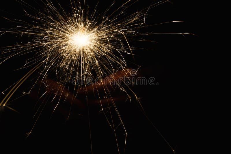 Cierge magique de partie de nouvelle année dans des mains femelles sur le fond noir image stock
