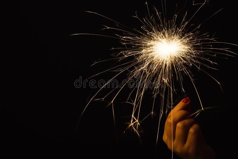 Cierge magique de partie de nouvelle année dans la main femelle sur le fond noir image stock