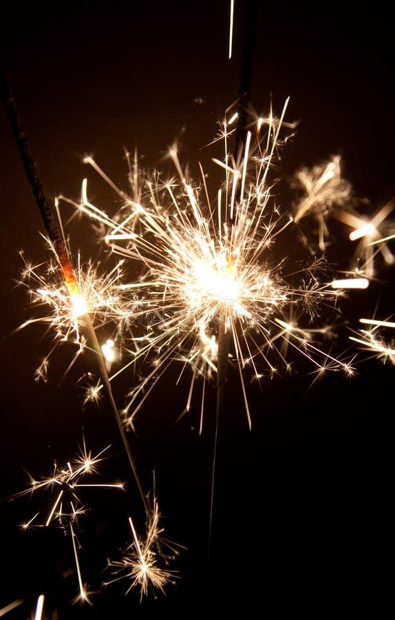 Cierge magique deux pendant la nuit avec un bon nombre d'étincelles image stock