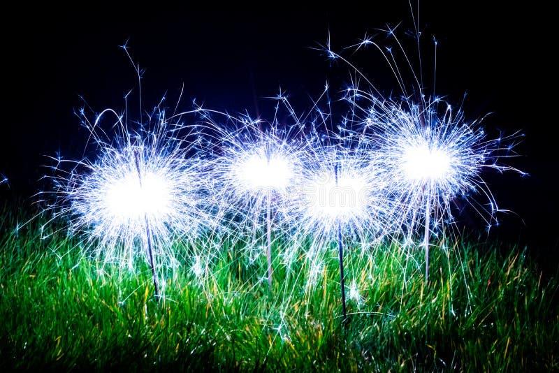 Cierges magiques bleus dans l'herbe image stock