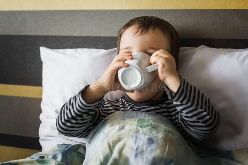 Cierpiąca mała chłopiec pije filiżankę medicament lying on the beach na łóżku fotografia stock