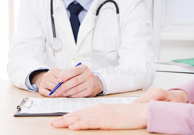 Cierpliwy słuchanie uważnie męska lekarka wyjaśnia cierpliwych objawy lub pyta pytanie gdy dyskutują papierkową robotę wpólnie obraz stock