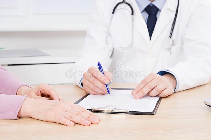 Cierpliwy słuchanie uważnie męska lekarka wyjaśnia cierpliwych objawy lub pyta pytanie gdy dyskutują papierkową robotę wpólnie zdjęcia stock
