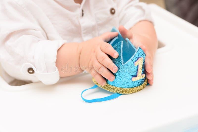 Cierra con la mano del bebé de feliz cumpleaños con la corona azul con el dígito uno foto de archivo