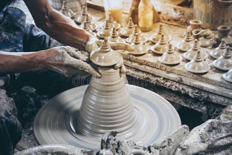 Cierra la mano de alfarero profesional haciendo tapa estilo tailandés sobre una rueda de alfarero en aldeas de cerámica en Ko Kre fotografía de archivo libre de regalías