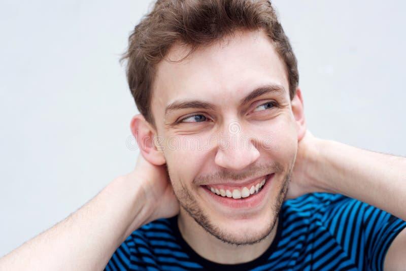 Cierra a un guapo joven sonriendo con las manos detrás de la cabeza por una pared blanca imagenes de archivo