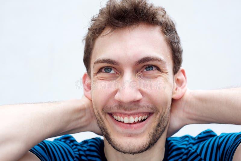 Cierra a un joven sonriendo con las manos detrás de la cabeza por el fondo blanco imágenes de archivo libres de regalías