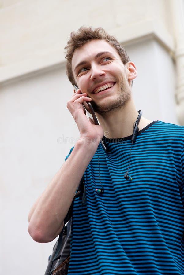 Cierra a un joven sonriendo y hablando con el teléfono móvil al aire libre imagen de archivo