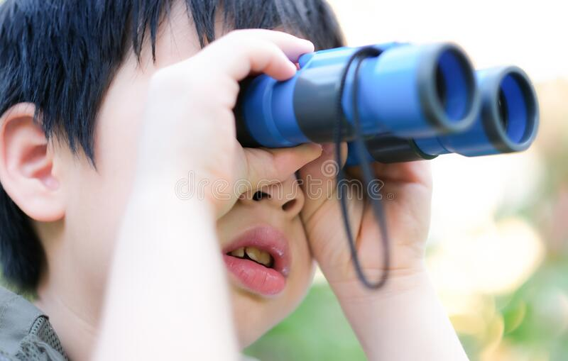 Cierra a un niño curioso asiático mirando a través de los prismáticos en el jardín imagen de archivo libre de regalías