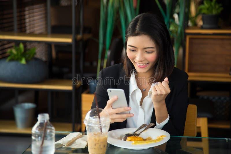 Cierra a una encantadora joven asiática vestida de forma formal sentada en una cafetería después del almuerzo, Ella sonríe recibi foto de archivo libre de regalías