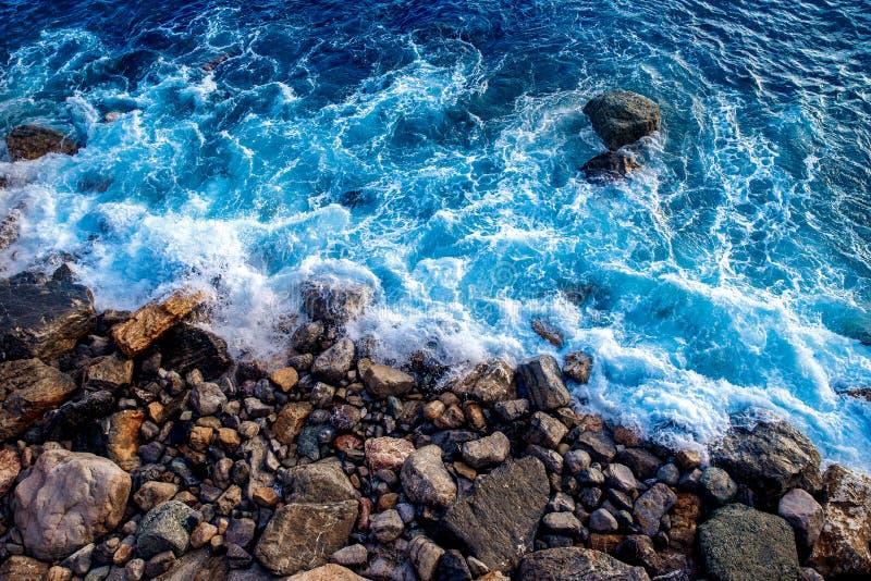 Cierre aéreo del abejón de la visión superior para arriba Las ondas del mar lavan la playa rocosa salvaje fotos de archivo libres de regalías