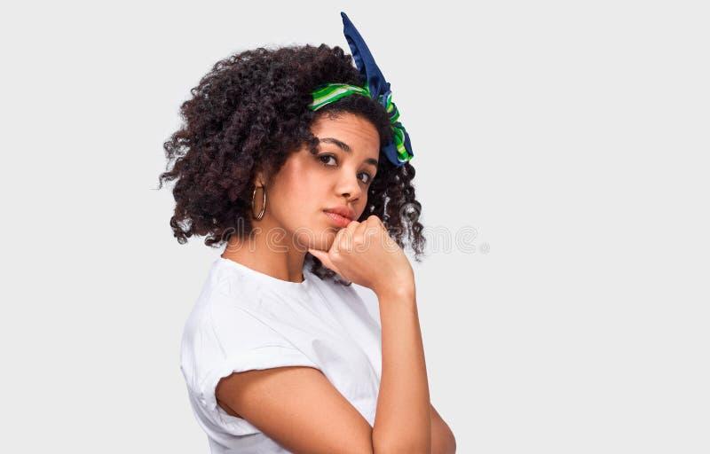 Cierre aislado del estudio encima del retrato de la mujer joven elegante con el pelo lanudo oscuro que toca su barbilla y que mir fotos de archivo libres de regalías