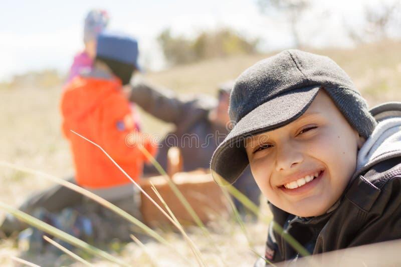 Cierre al aire libre de la sonrisa feliz de la comida campestre de los niños para arriba que miente en la hierba foto de archivo libre de regalías
