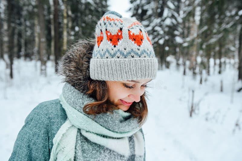 Cierre al aire libre encima del retrato de la muchacha feliz hermosa joven, sombrero hecho punto elegante del invierno que lleva foto de archivo libre de regalías