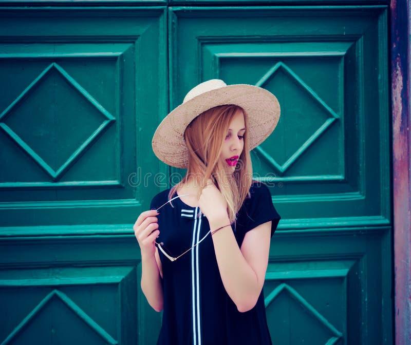 Cierre al aire libre encima del retrato de la mujer en vestido negro de moda, gafas de sol y sombrero amarillo Forma de vida de l fotografía de archivo