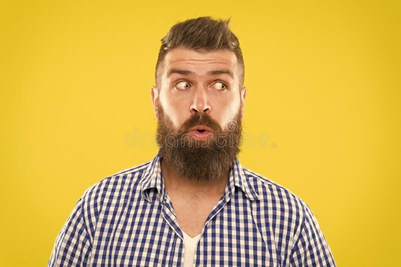 Cierre amarillo del fondo de la cara del inconformista barbudo del hombre que se pregunta para arriba Expresi?n sorprendida indiv fotografía de archivo