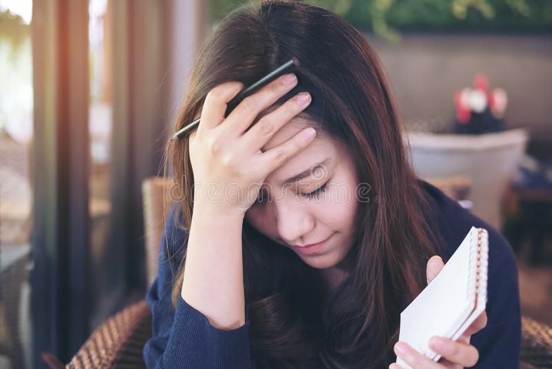 Cierre asiático de la mujer de negocios ella ojos que sostienen el cuaderno y el lápiz con la sensación subrayada y cansada imagen de archivo libre de regalías