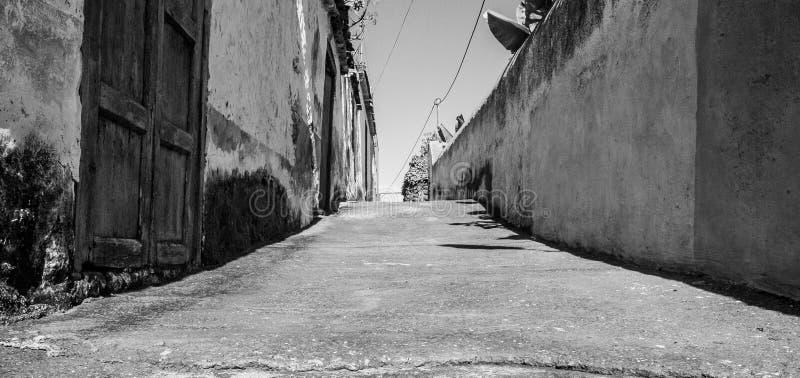 Cierre blanco y negro del arte para arriba de una pequeña calle imagenes de archivo