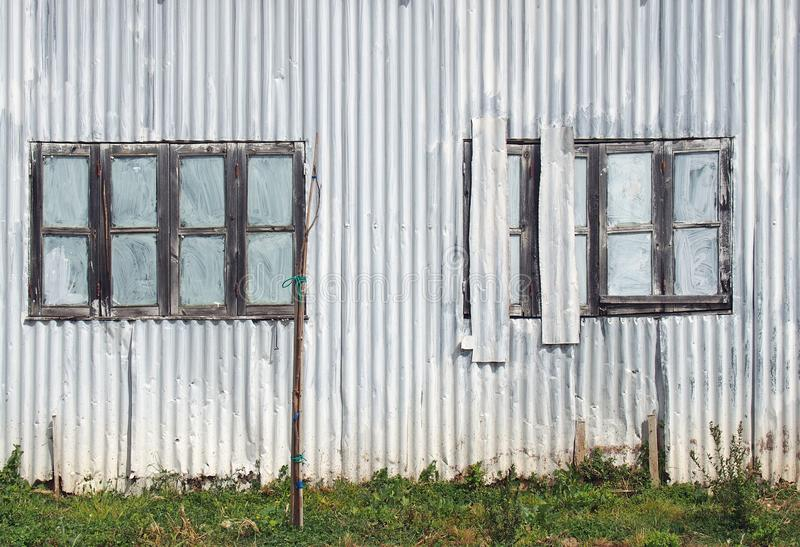 cierre completo del marco para arriba de un edificio dilapidado viejo lamentable del hierro acanalado con con cerrado pintado sob foto de archivo