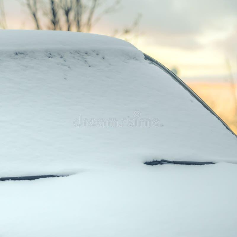 Cierre cuadrado claro para arriba de un vehículo negro nevoso con el horizonte en el fondo en la puesta del sol fotografía de archivo