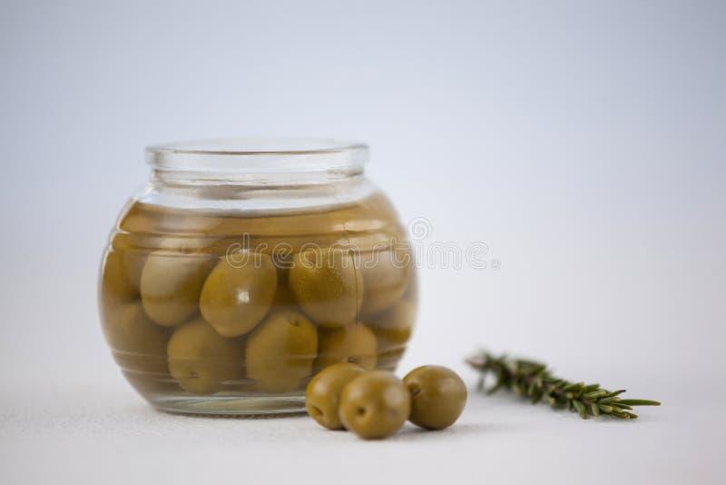 Cierre de aceitunas verdes en el tarro de cristal por la hierba imagenes de archivo