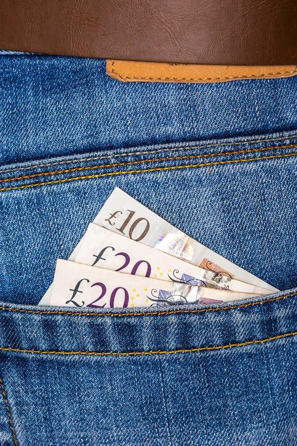 Cierre de billetes de 10 y 20 libras esterlinas asomándose al bolsillo de los jeans azules imágenes de archivo libres de regalías