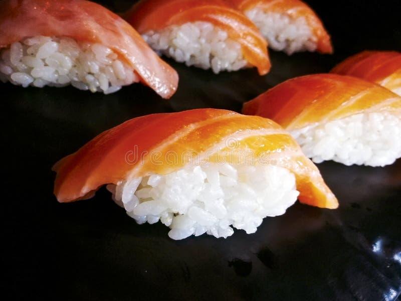 Cierre de color salmón del sushi del motivo de Nigiri para arriba en un plato negro imágenes de archivo libres de regalías