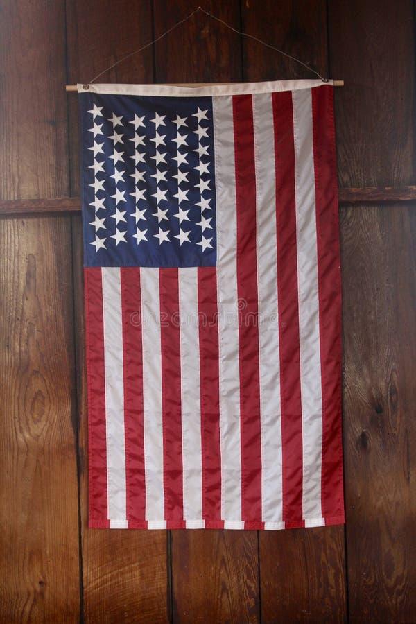 Cierre de la bandera americana encima del colgante verticalmente en la pared de madera imagen de archivo