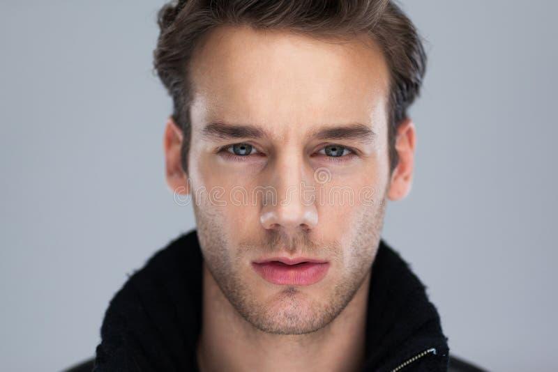 Cierre de la cara del hombre de la moda para arriba sobre fondo gris imagen de archivo libre de regalías