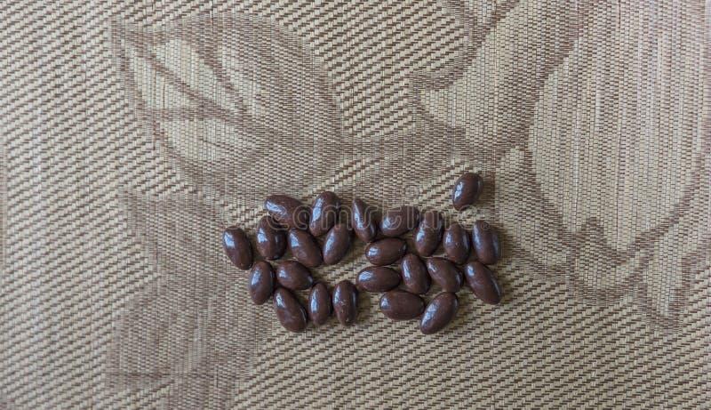 Cierre de la imagen de la comida encima del caramelo, chocolate caliente, nueces oscuras adicionales de la almendra Textura en fo foto de archivo