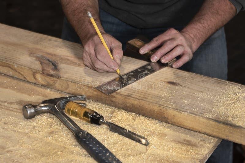 Cierre de la línea de señalización del carpintero en una tabla boscosa con lápiz y cuadrado de madera durante la remodelación del fotografía de archivo