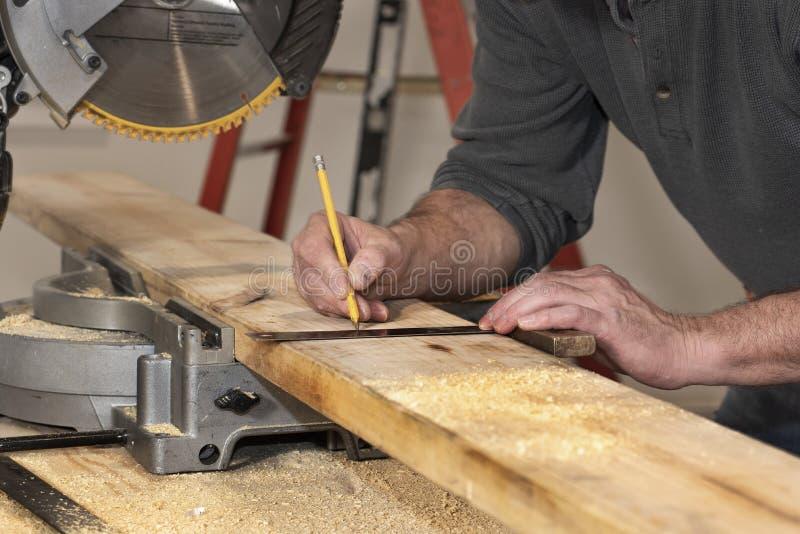 cierre de la línea de señalización del carpintero en una tabla boscosa con lápiz y cuadrado de madera durante la remodelación del fotos de archivo