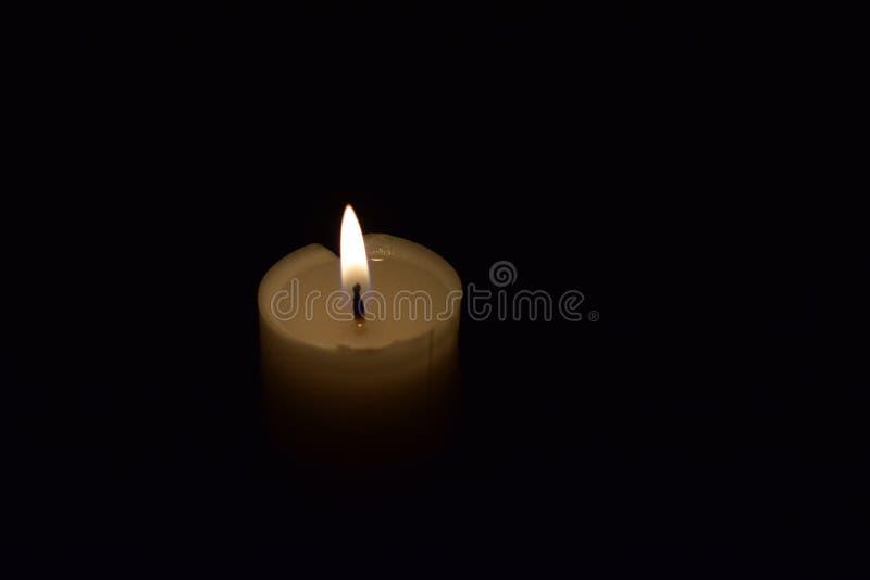 Cierre de la llama de la luz de la vela para arriba con el fondo negro imágenes de archivo libres de regalías