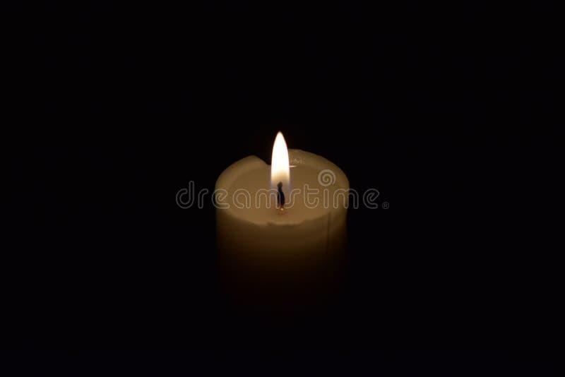 Cierre de la llama de la luz de la vela para arriba con el fondo negro foto de archivo