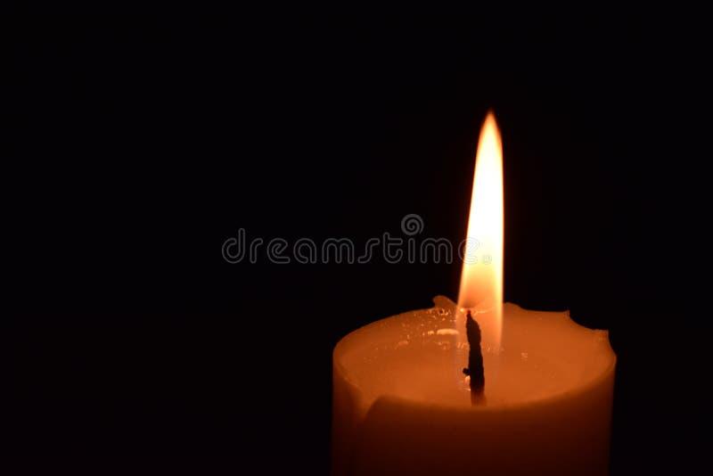 Cierre de la llama de la luz de la vela para arriba con el fondo negro fotografía de archivo libre de regalías
