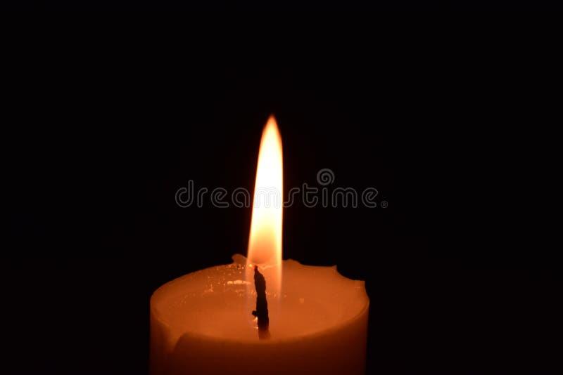 Cierre de la llama de la luz de la vela para arriba con el fondo negro imagenes de archivo