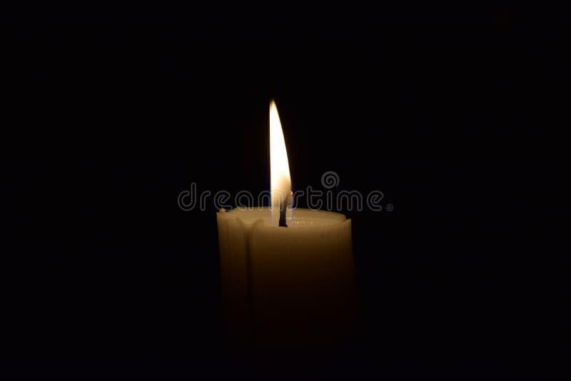Cierre de la llama de la luz de la vela para arriba con el fondo negro imagen de archivo