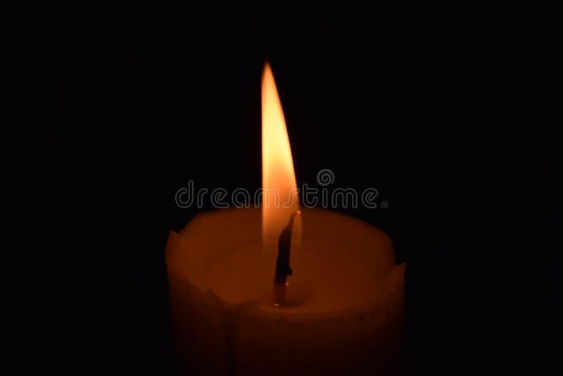 Cierre de la llama de la luz de la vela para arriba con el fondo negro fotos de archivo libres de regalías