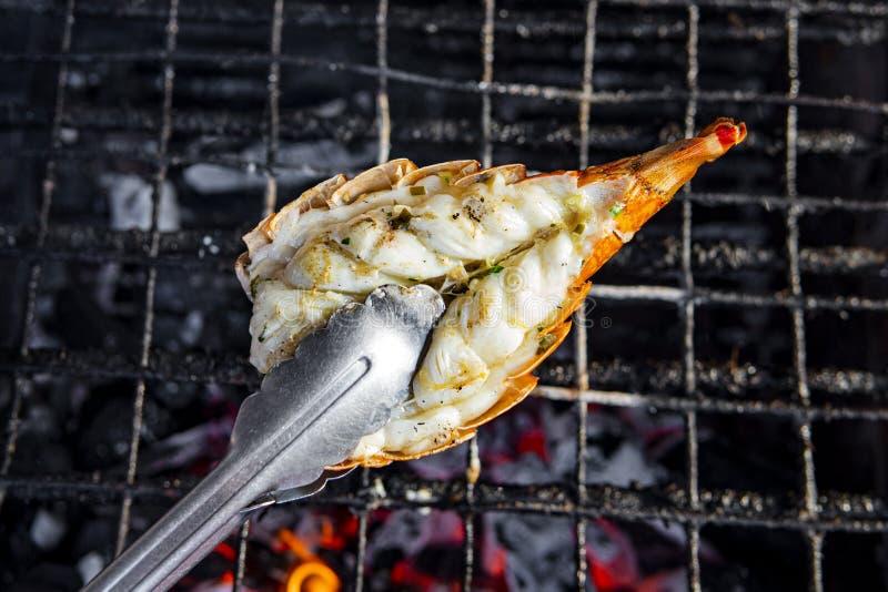 Cierre de la mano de Cook Grilling Big Lobster en barbacoa Famosa comida callejera en Bangkok, Tailandia para turistas fotos de archivo libres de regalías
