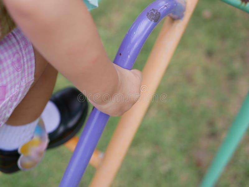 Cierre de la mano de poco bebé detener en las escaleras metálicas en un patio que aprende subirlo para arriba imagenes de archivo